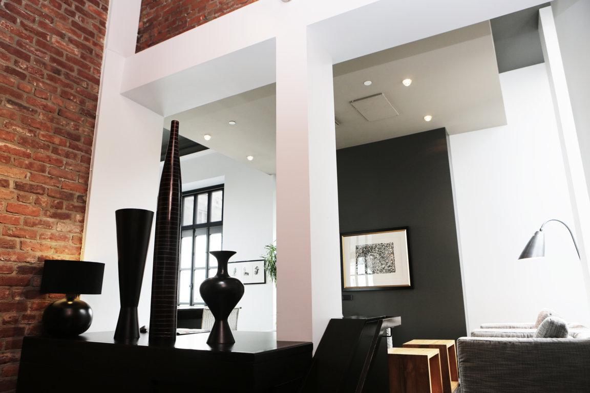 Appartement contemporain à dominante blanc et noir pour faire ressortir le mur de briques