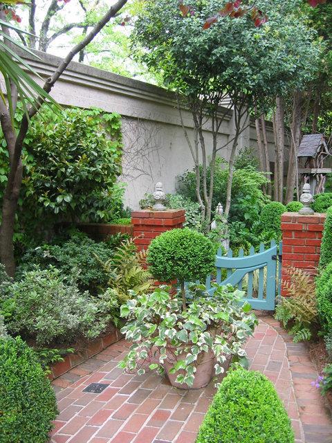 Petit jardin clos de massifs au sol en briques rouges Petit portillon de bois peint de couleur vive